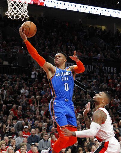 Oklahoma City Thunder guard Russell Westbrook, left, shoots as Portland Trail Blazers guard Damian Lillard, right, defends during the first half of Game 1 of a first-round NBA basketball playoff series in Portland, Ore., Sunday, April 14, 2019.