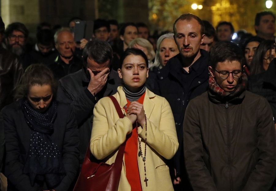 People pray as Notre Dame cathedral burns in Paris, Monday.