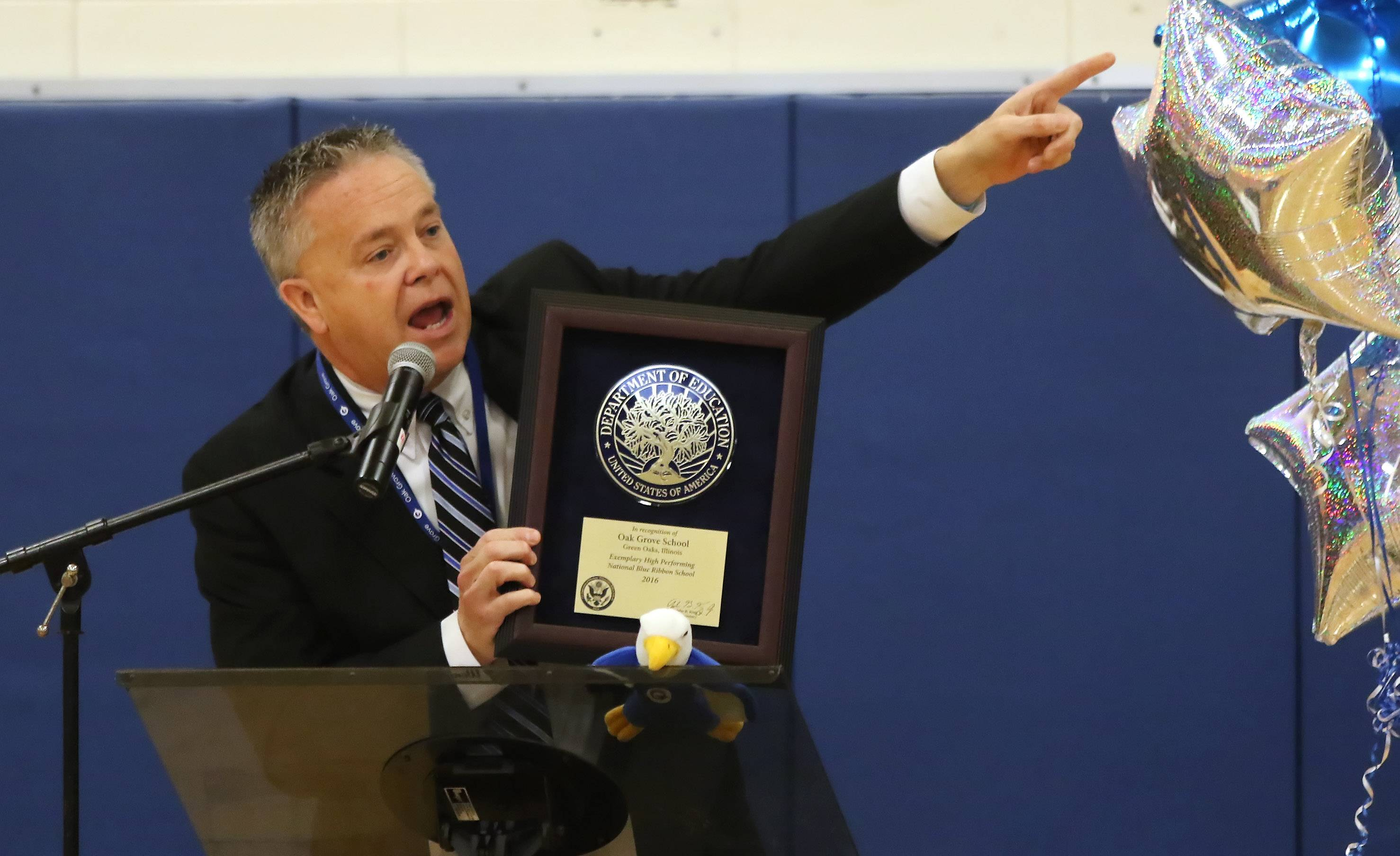 Superintendent Lonny Lemon displays a plaque recognizing Oak Grove School as a National Blue Ribbon School during an assembly in 2016. Lemon is retiring in 2020.