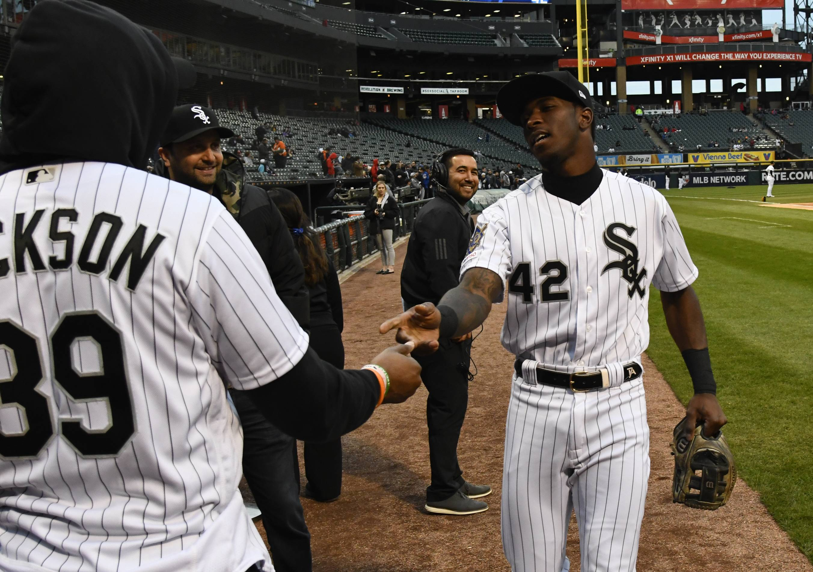 Chicago Bears player Eddie Jackson, left, and Chicago White Sox shortstop Tim Anderson, right, shake hands before Jackson threw out a ceremonial first pitch before a baseball game between the White Sox and the Kansas City Royals, Monday, April 15, 2019, in Chicago. No. 42 was worn to honor Jackie Robinson.