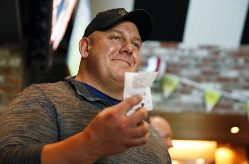 James Adducci holds up his winning ticket after winning more than one million dollars betting on Tiger Woods winning the Masters, Monday, April 15, 2019, in Las Vegas.