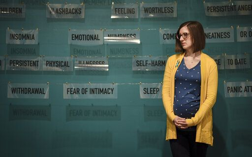 Melissa Hudecz, co-curator of the 'Finding Our Voice: Sister Survivors Speak' exhibit, stands in front one of the pieces in the MSU Museum's exhibit in East Lansing, Mich., Monday, April 15, 2019. The exhibit reflects on the sexual abuse centered on the Michigan State University campus in recent years. (Matthew Dae Smith/Lansing State Journal via AP)