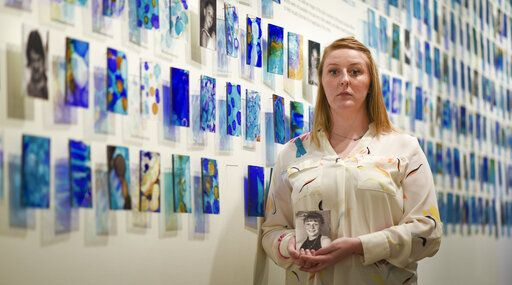Amanda Smith, co-curator of the 'Finding Our Voice: Sister Survivors Speak' exhibit, stands in front one of the pieces in the MSU Museum's exhibit in East Lansing, Mich., Monday, April 15, 2019. Smith holds a picture of herself at the age when Larry Nassar's abuse began. The show opens April 16 and runs through March of 2020. (Matthew Dae Smith/Lansing State Journal via AP)