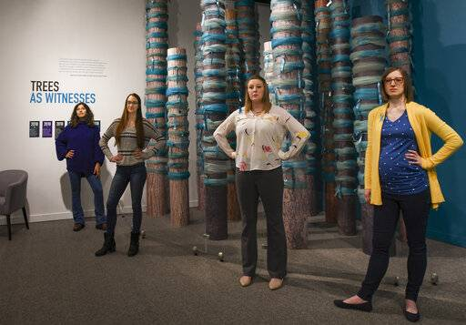 Curators of the 'Finding Our Voice: Sister Survivors Speak' exhibit, from left, Jordyn Fishman, Katie Black, Amanda Smith, and Melissa Hudecz pose for a photo in the MSU Museum's main gallery in East Lansing, Mich., Monday, April 15, 2019. The exhibit reflects on the sexual abuse centered on the Michigan State University campus in recent years. (Matthew Dae Smith/Lansing State Journal via AP)