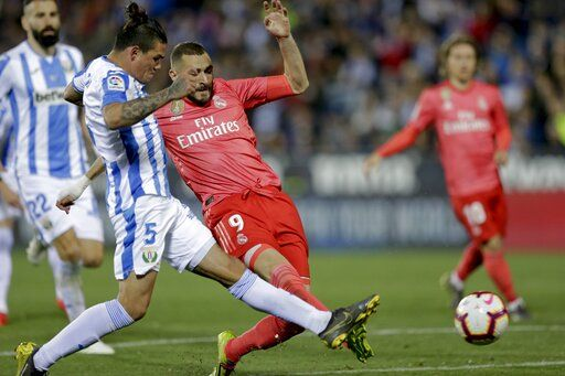 Real Madrid's Karim Benzema duels for the ball against Leganes' Jonathan Cristian, left, Silva during a Spanish La Liga soccer match in Leganes, outskirts Madrid, Spain, Monday, April 15, 2019.