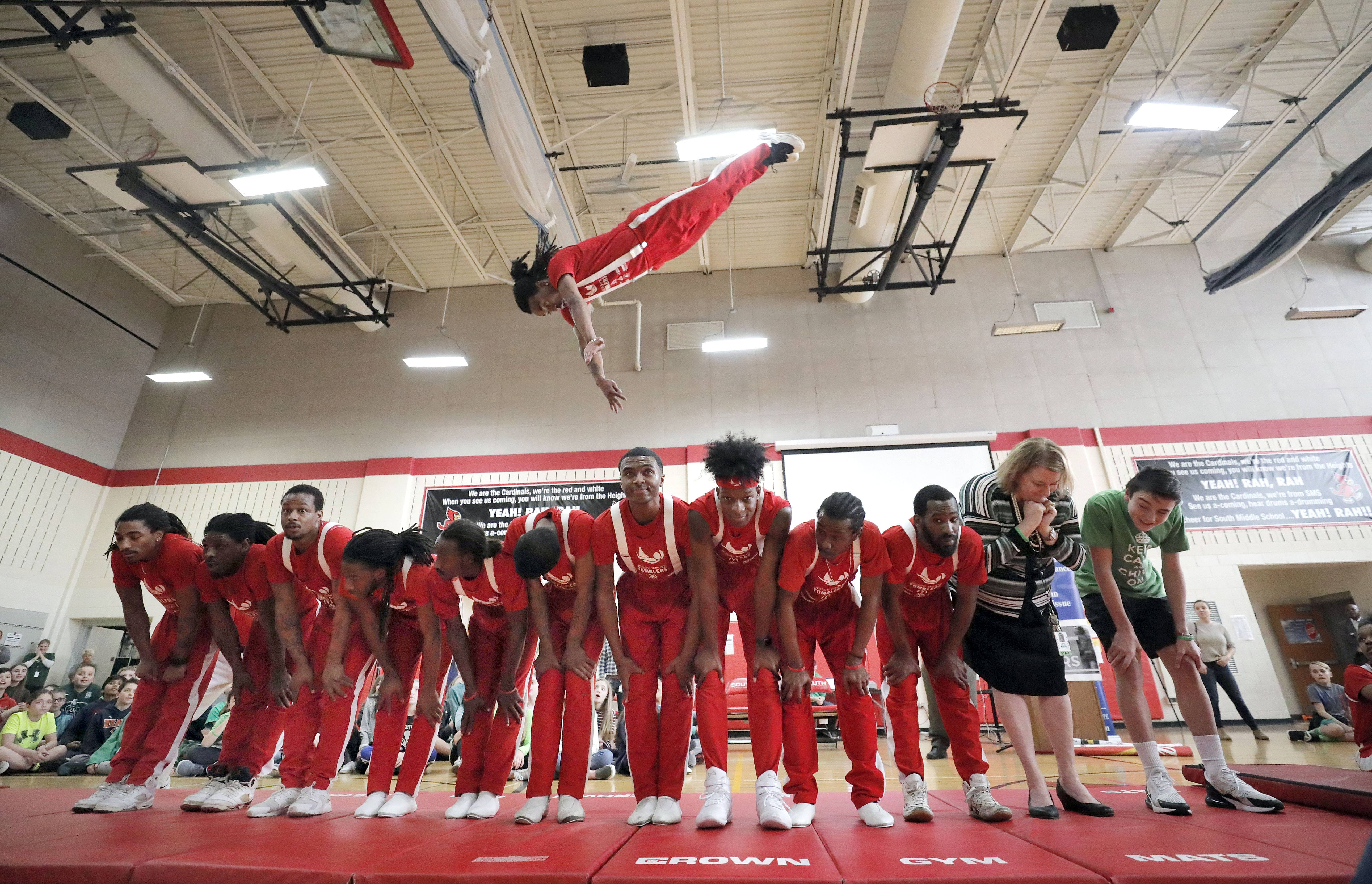 Taylor Petrillo, from right, and South Middle School Principal Piper Boston join the Jesse White Tumblers Tuesday afternoon during a performance in the Arlington Heights school's gym. Taylor organized the all-school assembly to honor organ donors, including his 27-year-old brother Matthew, who died in September.
