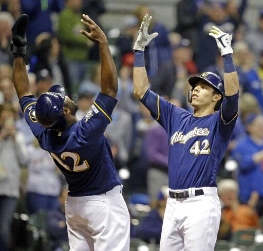 Milwaukee Brewers' Christian Yelich, right, reacts with Lorenzo Cain after hitting a three-run home run against the St. Louis Cardinals during the sixth inning of a baseball game Monday, April 15, 2019, in Milwaukee.