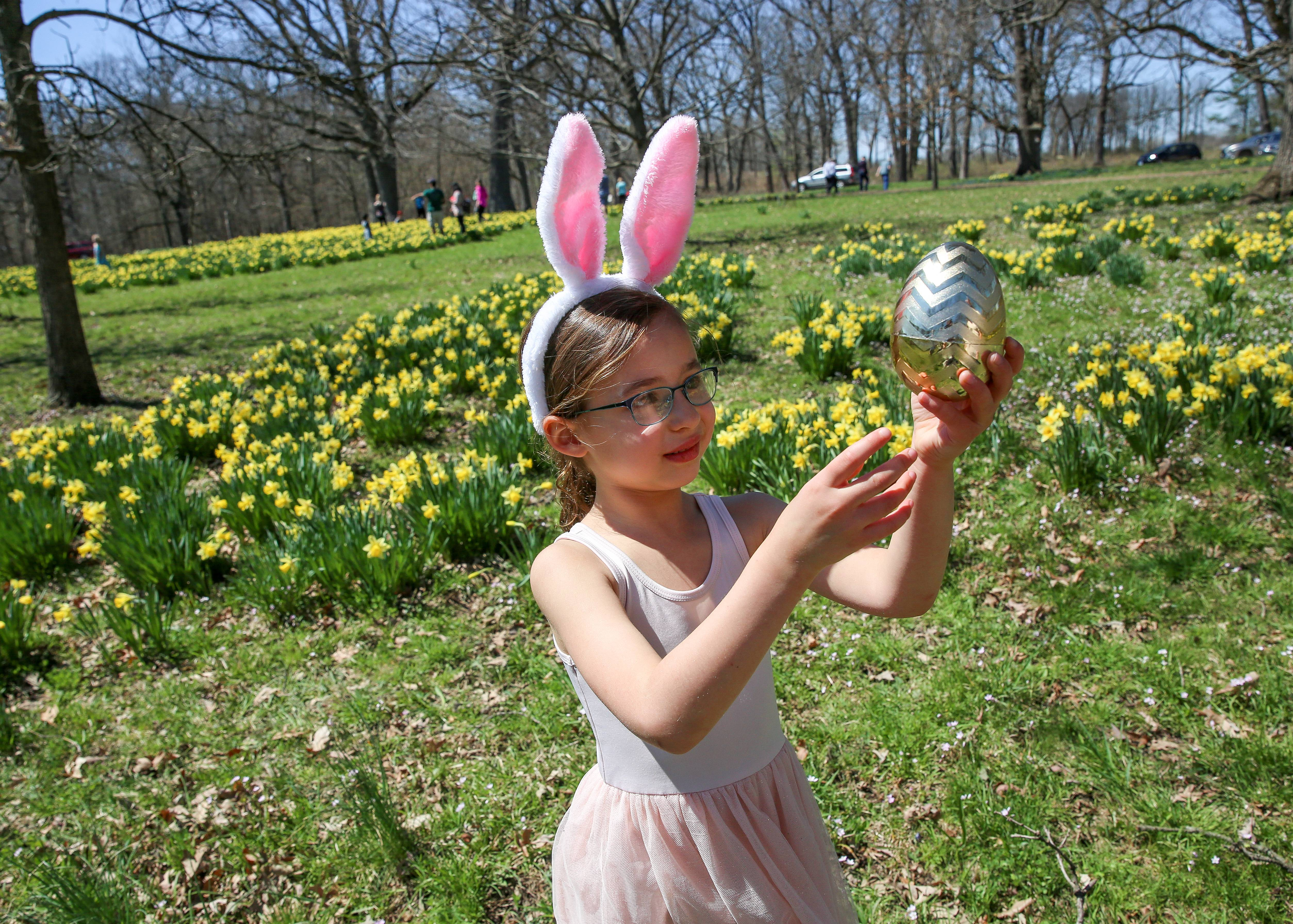 Eliana Gilbert, 5, of Arlington Heights, shows off one of her Easter eggs as she visits the Morton Arboretum in Lisle with her family to see the daffodils in bloom.