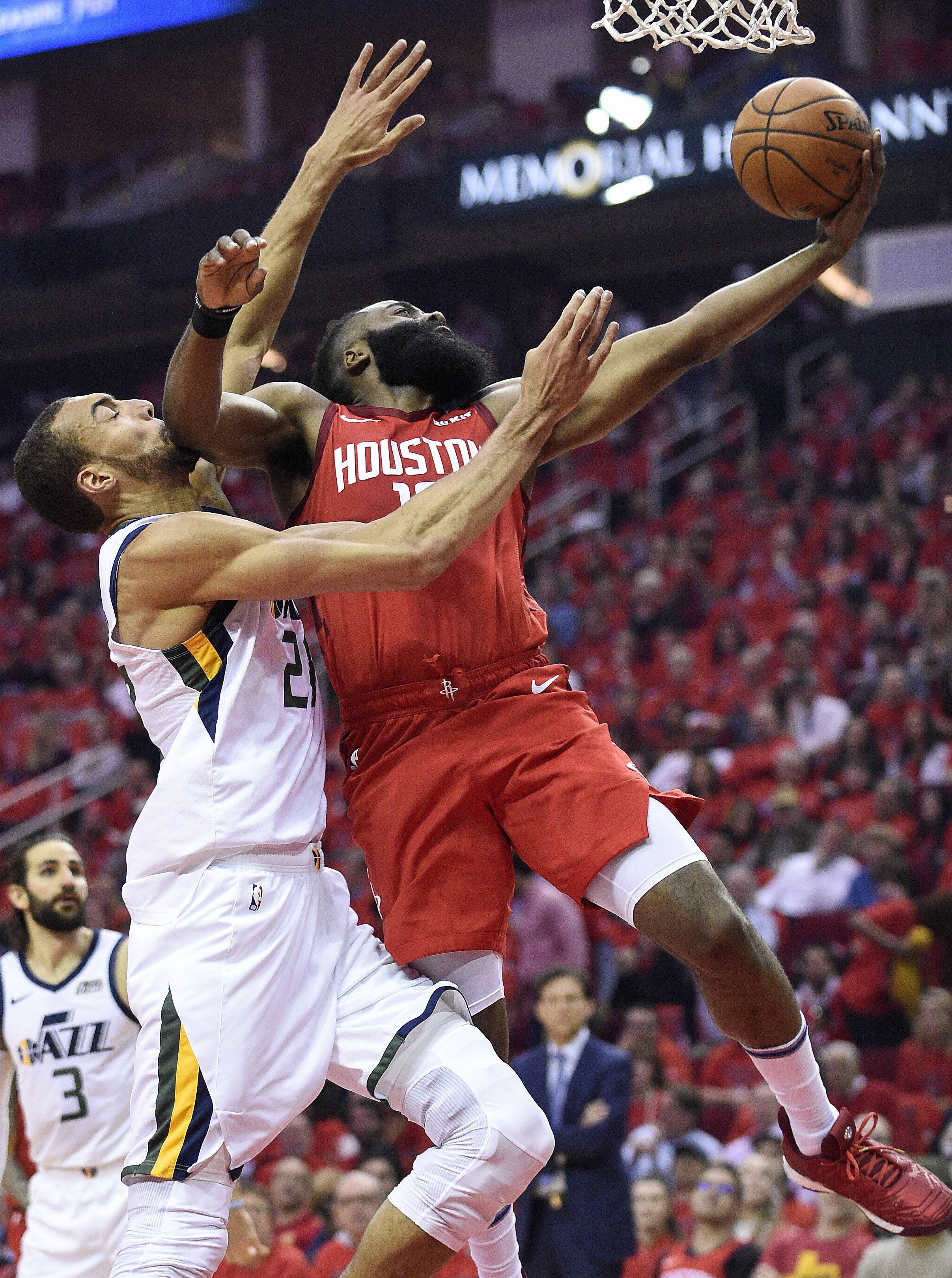 Houston Rockets guard James Harden, right, drives to the basket as Utah Jazz center Rudy Gobert defends during the first half of Game 1, Sunday in Houston. Harden averaged 36.1 points this season