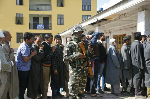 An Indian paramilitary soldier stands guard as Kashmiri voters wait in a queue to cast their votes outside a polling station during the second phase of India's general elections, on the outskirts of Srinagar, Indian controlled Kashmir, Thursday, April 18, 2019. Kashmiri separatist leaders who challenge India's sovereignty over the disputed region have called for a boycott of the vote. Most polling stations in Srinagar and Budgam areas of Kashmir looked deserted in the morning with more armed police, paramilitary soldiers and election staff present than voters.