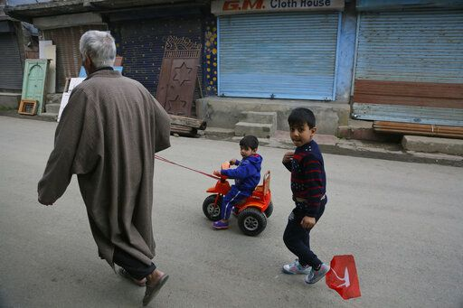 An elderly Kashmiri man pulls a child on a tricycle during a strike called on the second phase of India's general elections, in Srinagar, Indian controlled Kashmir, Thursday, April 18, 2019. Kashmiri separatist leaders who challenge India's sovereignty over the disputed region have called for a boycott of the vote. Most polling stations in Srinagar and Budgam areas of Kashmir looked deserted in the morning with more armed police, paramilitary soldiers and election staff present than voters.