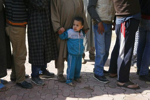 A boy stands holding the hand of a Kashmiri voter waiting in a queue to cast his vote, outside a poling station during the second phase of India's general elections on the outskirts of Srinagar, Indian controlled Kashmir, Thursday, April 18, 2019. Kashmiri separatist leaders who challenge India's sovereignty over the disputed region have called for a boycott of the vote. Most polling stations in Srinagar and Budgam areas of Kashmir looked deserted in the morning with more armed police, paramilitary soldiers and election staff present than voters.