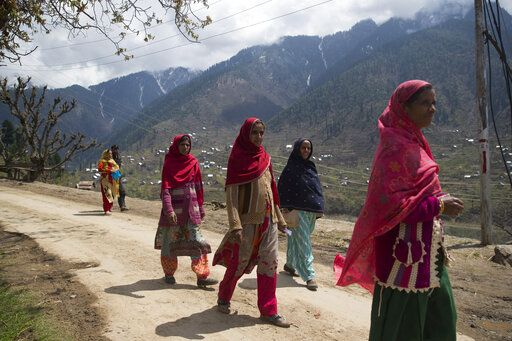 Kashmiri women walk back from a polling station during the second phase of India's general elections, in Baba Nagri, about 44 kilometers (28 miles) northeast of Srinagar, Indian controlled Kashmir, Thursday, April 18, 2019. Kashmiri separatist leaders who challenge India's sovereignty over the disputed region have called for a boycott of the vote. Most polling stations in Srinagar and Budgam areas of Kashmir looked deserted in the morning with more armed police, paramilitary soldiers and election staff present than voters.