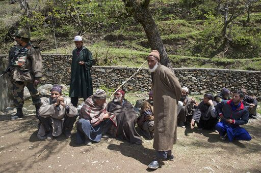 Elderly Kashmiri voters wait to cast their votes, outside a polling station during the second phase of India's general elections in Baba Nagri, about 44 kilometers (28 miles) northeast of Srinagar, Indian controlled Kashmir, Thursday, April 18, 2019. Kashmiri separatist leaders who challenge India's sovereignty over the disputed region have called for a boycott of the vote. Most polling stations in Srinagar and Budgam areas of Kashmir looked deserted in the morning with more armed police, paramilitary soldiers and election staff present than voters.