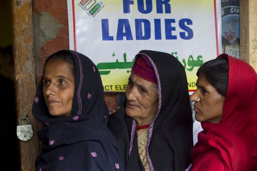 Kashmiri women wait in a queue to cast their votes during the second phase of India's general elections, in Baba Nagri, about 44 kilometers (28 miles) northeast of Srinagar, Indian controlled Kashmir, Thursday, April 18, 2019. Kashmiri separatist leaders who challenge India's sovereignty over the disputed region have called for a boycott of the vote. Most polling stations in Srinagar and Budgam areas of Kashmir looked deserted in the morning with more armed police, paramilitary soldiers and election staff present than voters.