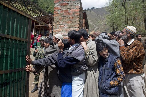 Kashmiri voters stand in a queue outside a polling station during the second phase of India's general elections, in Baba Nagri, about 44 kilometers (28 miles) northeast of Srinagar, Indian controlled Kashmir, Thursday, April 18, 2019. Kashmiri separatist leaders who challenge India's sovereignty over the disputed region have called for a boycott of the vote. Most polling stations in Srinagar and Budgam areas of Kashmir looked deserted in the morning with more armed police, paramilitary soldiers and election staff present than voters.