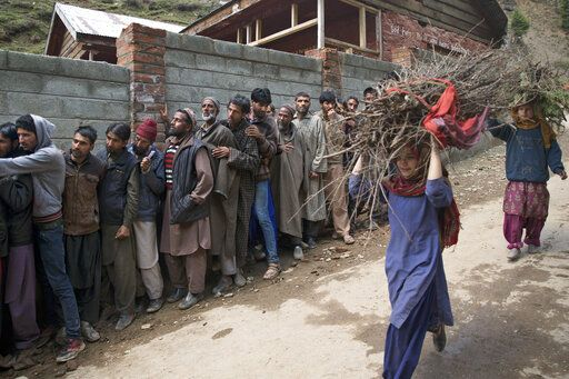 Young Kashmiri girls carry firewood and walk past voters standing in a queue outside a polling station during the second phase of India's general elections, in Baba Nagri, about 44 kilometers (28 miles) northeast of Srinagar, Indian controlled Kashmir, Thursday, April 18, 2019. Kashmiri separatist leaders who challenge India's sovereignty over the disputed region have called for a boycott of the vote. Most polling stations in Srinagar and Budgam areas of Kashmir looked deserted in the morning with more armed police, paramilitary soldiers and election staff present than voters.