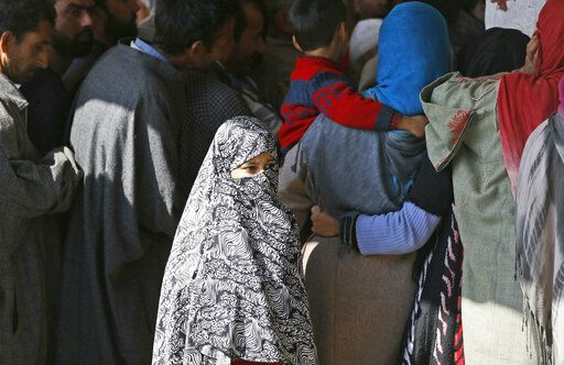 A young Kashmiri woman walks past voters standing in a queue to cast their votes at a polling station during the second phase of India's general elections, on the outskirts of Srinagar, Indian controlled Kashmir, Thursday, April 18, 2019. Kashmiri separatist leaders who challenge India's sovereignty over the disputed region have called for a boycott of the vote. Most polling stations in Srinagar and Budgam areas of Kashmir looked deserted in the morning with more armed police, paramilitary soldiers and election staff present than voters.