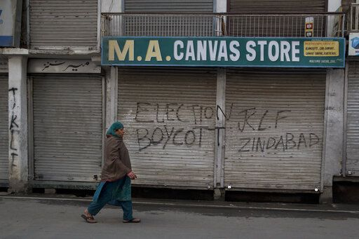 A Kashmiri woman walks past an anti-election graffiti on the shutters of a shop during the second phase of India's general elections, in Srinagar, Indian controlled Kashmir, Thursday, April 18, 2019. Kashmiri separatist leaders who challenge India's sovereignty over the disputed region have called for a boycott of the vote. Most polling stations in Srinagar and Budgam areas of Kashmir looked deserted in the morning with more armed police, paramilitary soldiers and election staff present than voters.
