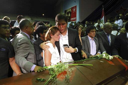 People embrace by the coffin of former President Alan Garcia during his wake at his party's headquarters in Lima, Peru, Wednesday, April 17, 2019. Garcia shot himself in the head and died Wednesday as officers waited to arrest him in a massive graft probe that has put the country's most prominent politicians behind bars and provoked a reckoning over corruption.
