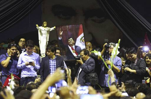 People hold a photo of Peru's late President Alan Garcia at his party's headquarters where his wake takes place in Lima, Peru, Wednesday, April 17, 2019. Garcia shot himself in the head and died Wednesday as officers waited to arrest him in a massive graft probe that has put the country's most prominent politicians behind bars and provoked a reckoning over corruption.