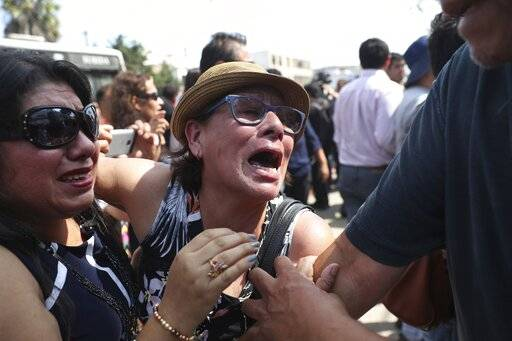 Supporters of former Peruvian President Alan Garcia cry as they learn that the former leader died from a self-inflicted gun shot, outside the hospital where he was taken after he shot himself, in Lima, Peru, Wednesday, April 17, 2019. Peru's current President Martinez Vizcarra said Garcia, the 69-year-old former head of state died after undergoing emergency surgery. Garcia shot himself in the head early Wednesday as police came to detain him in connection with a corruption probe.
