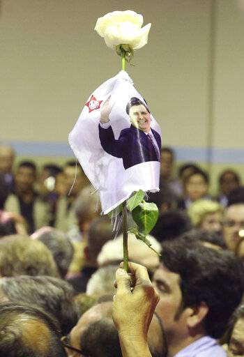 A person holds up a flower with a photo of Peru's late President Alan Garcia during his wake at his party's headquarters in Lima, Peru, Wednesday, April 17, 2019. Garcia shot himself in the head and died Wednesday as officers waited to arrest him in a massive graft probe that has put the country's most prominent politicians behind bars and provoked a reckoning over corruption.