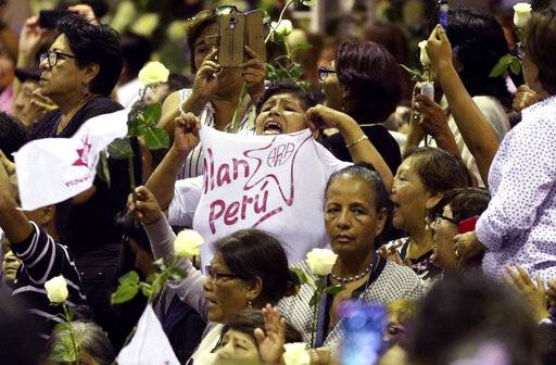 "A woman holds out her shirt that reads in Spanish ""Alan Peru"" during his wake at his party's headquarters in Lima, Peru, Wednesday, April 17, 2019. Garcia shot himself in the head and died Wednesday as officers waited to arrest him in a massive graft probe that has put the country's most prominent politicians behind bars and provoked a reckoning over corruption."