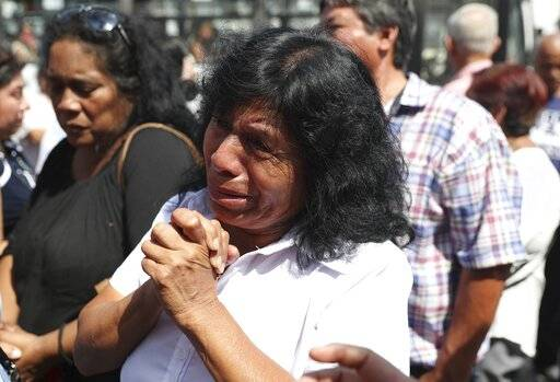A supporter of former Peruvian President Alan Garcia grieves after learning that the former leader died from a self-inflicted gun shot, outside the hospital where he was taken after he shot himself, in Lima, Peru, Wednesday, April 17, 2019. Peru's current President Martinez Vizcarra said Garcia, the 69-year-old former head of state died after undergoing emergency surgery. Garcia shot himself in the head early Wednesday as police came to detain him in connection with a corruption probe.