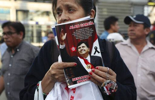 A woman sells photos and a keychain featuring Peru's late President Alan Garcia outside his party's headquarters before the start of his wake in Lima, Peru, Wednesday, April 17, 2019. Garcia shot himself in the head and died Wednesday as officers waited to arrest him in a massive graft probe that has put the country's most prominent politicians behind bars and provoked a reckoning over corruption.