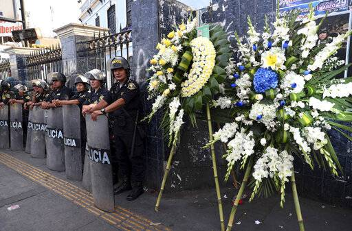 Flowers stand outside the party headquarters of Peru's late President Alan Garcia soon before his wake takes place in Lima, Peru, Wednesday, April 17, 2019. Garcia shot himself in the head and died Wednesday as officers waited to arrest him in a massive graft probe that has put the country's most prominent politicians behind bars and provoked a reckoning over corruption.