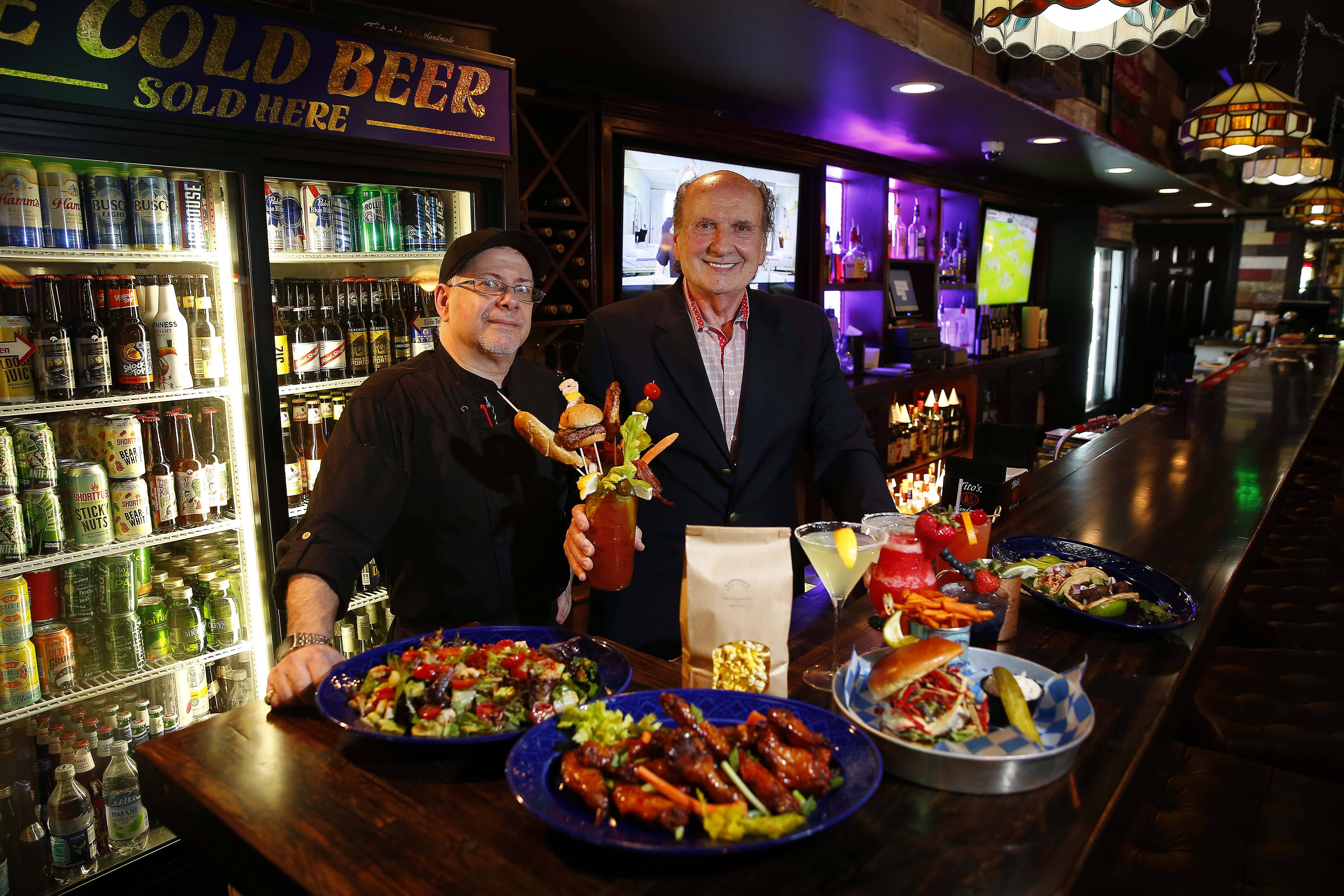 Chef Steve Loftis, left, and owner Tony Bellino show off a variety of fare at Cattleman's Burger and Brew in Algonquin.