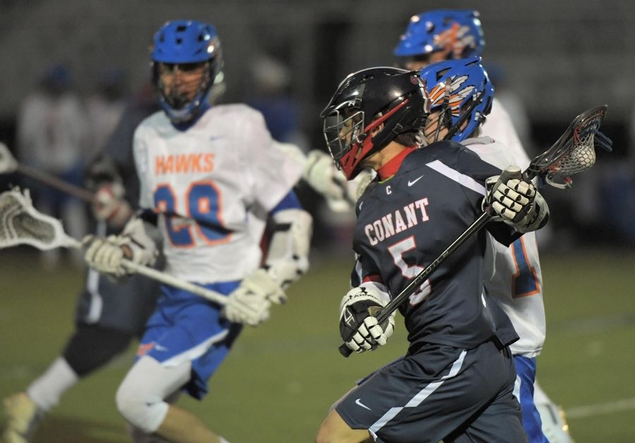 Conant's Jake Cosentino works against a host of Hoffman Estates players in a boys lacrosse game in Hoffman Estates Thursday.