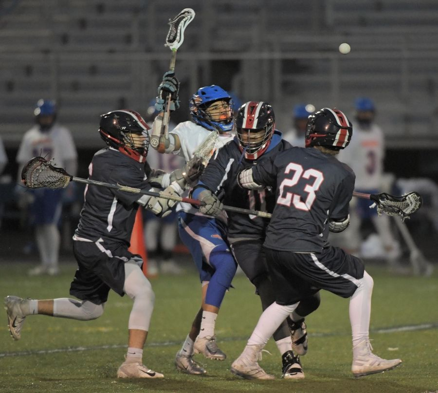 Conant's Kris Tohchev, Ethan Richert and Matt Ilnychyj tangle with Hoffman Estates' Alex Rodriguez in a boys lacrosse game in Hoffman Estates Thursday.