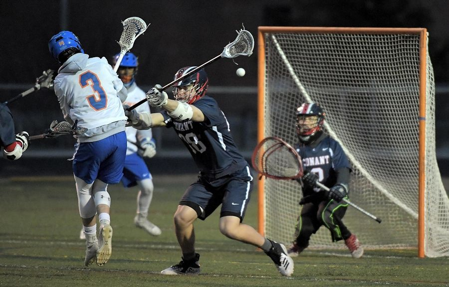 Conant's Derek Lewandowski defends against Hoffman Estates' Stefan Knappik as he shoots in a boys lacrosse game in Hoffman Estates Thursday.