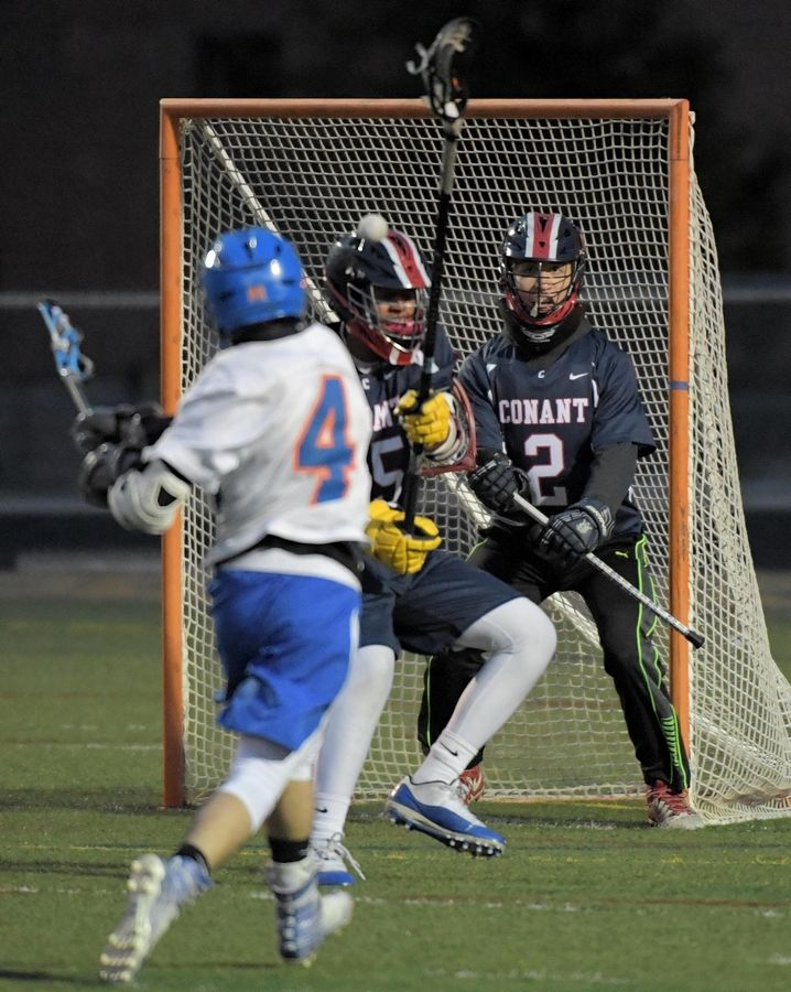 Hoffman Estates' Drew Eiring takes a shot that bounces off Conant's Kush Bhatt as goalkeeper Eric Braun watches in a boys lacrosse game in Hoffman Estates Thursday.