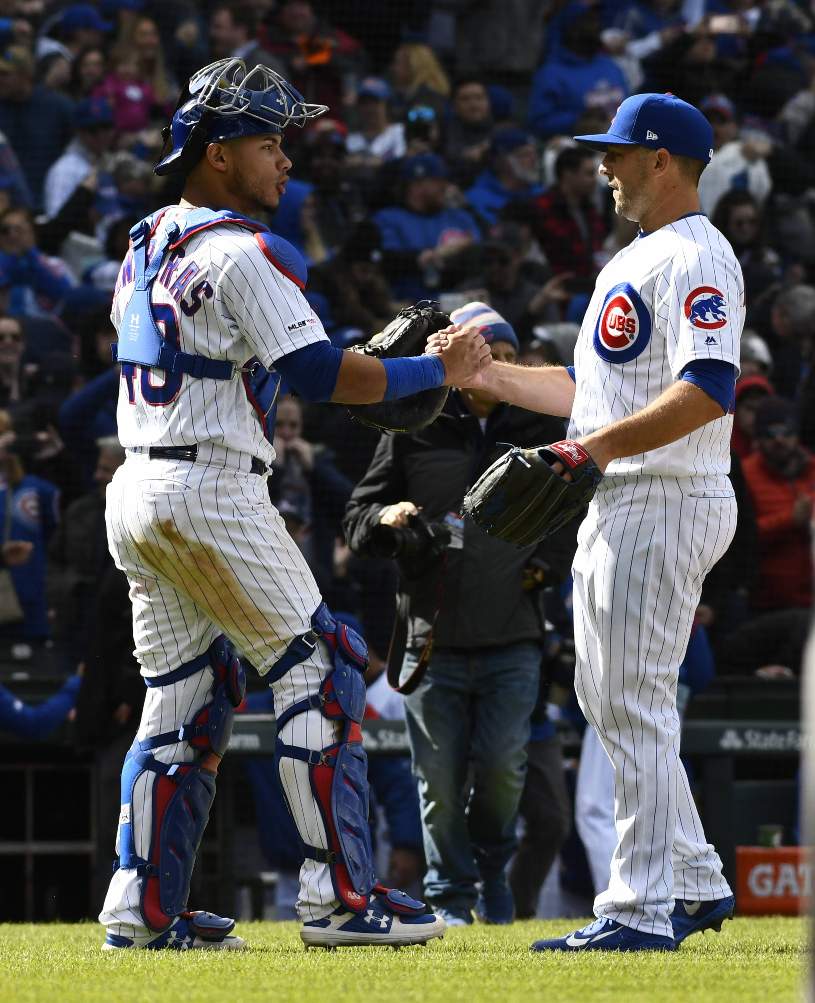 Chicago Cubs catcher Willson Contreras, left, and relief pitcher Brandon Kintzler, right, celebrate after a baseball game against the Los Angeles Angels, Friday, April 12, 2019, in Chicago. (AP Photo/Matt Marton)