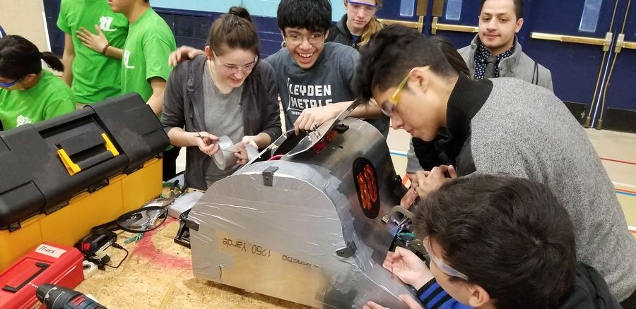 Members of Leyden's Engineering Club work on Edwin, the robot they designed and built for the annual Robot Rumble competition held at Prospect High School. Club members from each campus built a robot and participated in the event.