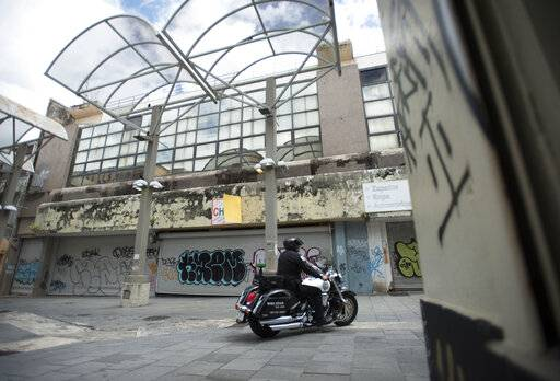 A municipal police officer drives past shuttered shops in the Paseo de Diego of San Juan, Puerto Rico, Wednesday, April 17, 2019. Many Puerto Ricans have left for Florida and New York.