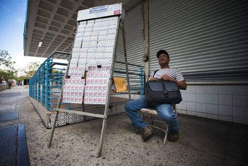 Lottery vendor Manuel Almonte waits for customers in the sparce Rio Piedras area of San Juan, Puerto Rico, Wednesday, April 17, 2019. The heaviest population drops in Puerto Rico since Hurricane Maria have occurred in metropolitan areas such as the capital and the city of Ponce.
