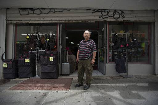 Luggage seller Jose Forteza, 88, poses for a portrait outside his store, one of the few still open in the Paseo de Diego of San Juan, Puerto Rico, Wednesday, April 17, 2019. Paseo de Diego, the central thoroughfare in Rio Piedras, was filled years ago with stores that are closed and empty today.