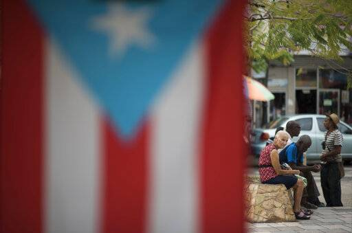 "Residents sit outside the Plaza del Mercado in the Rio Piedras area of San Juan, Puerto Rico, Wednesday, April 17, 2019, where a Puerto Rican flag hangs. ""You see fewer people around, fewer young people,"" said Wilfredo Montañez, 52, who was sitting on a bench in the plaza."
