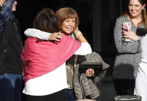 Roxanne Ballard, left, greets another woman as she arrives to attend a faith-based memorial service for the victims of the massacre at Columbine High School nearly 20 years earlier, at a community church, Thursday, April 18, 2019, in Littleton, Colo.
