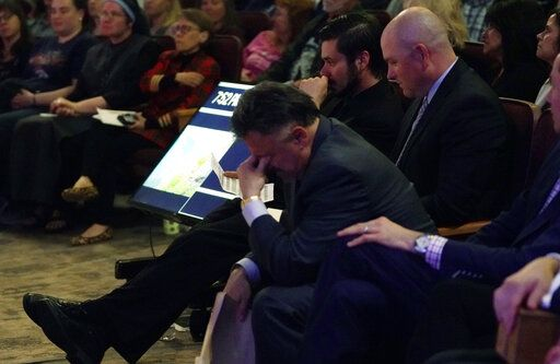 Frank DeAngelis, center, who was principal of Columbine High School during the massacre nearly 20 years earlier, fights back tears during a faith-based memorial service for the victims of the massacre, at a community church, Thursday, April 18, 2019, in Littleton, Colo. (Rick Wilking/Pool Photo via AP)