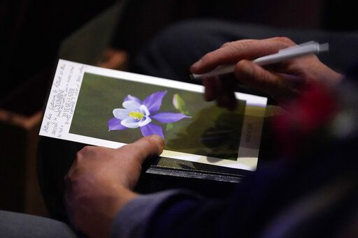An attendee holds a program at a faith-based memorial service for the victims of the massacre at Columbine High School nearly 20 years earlier, at a community church, Thursday, April 18, 2019, in Littleton, Colo. (Rick Wilking/Pool Photo via AP)