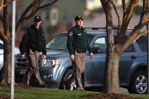 Jefferson County Sheriff's Department deputies walk the parking lot as participants arrive to attend a faith-based memorial service for the victims of the massacre at Columbine High School nearly 20 years ago at a community church Thursday, April 18, 2019, in Littleton, Colo.