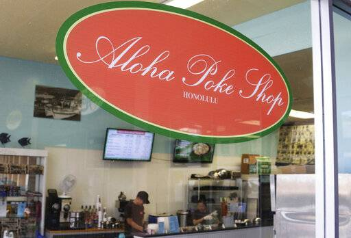 "This Tuesday, April 16, 2019, photo shows Aloha Poke Shop, a store in Honolulu that received a letter from Chicago-based Aloha Poke Co. saying the Illinois company had trademarked ""Aloha Poke"" and the Hawaii company would need to change its name. Hawaii lawmakers are considering adopting a resolution calling for the creation of legal protections for Native Hawaiian cultural intellectual property."