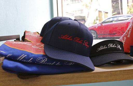 "This Tuesday, April 16, 2019, photo shows merchandise at Aloha Poke Shop, a store in Honolulu that received a letter from Chicago-based Aloha Poke Co. saying the Illinois company had trademarked ""Aloha Poke"" and the Hawaii company would need to change its name. Hawaii lawmakers are considering adopting a resolution calling for the creation of legal protections for Native Hawaiian cultural intellectual property."