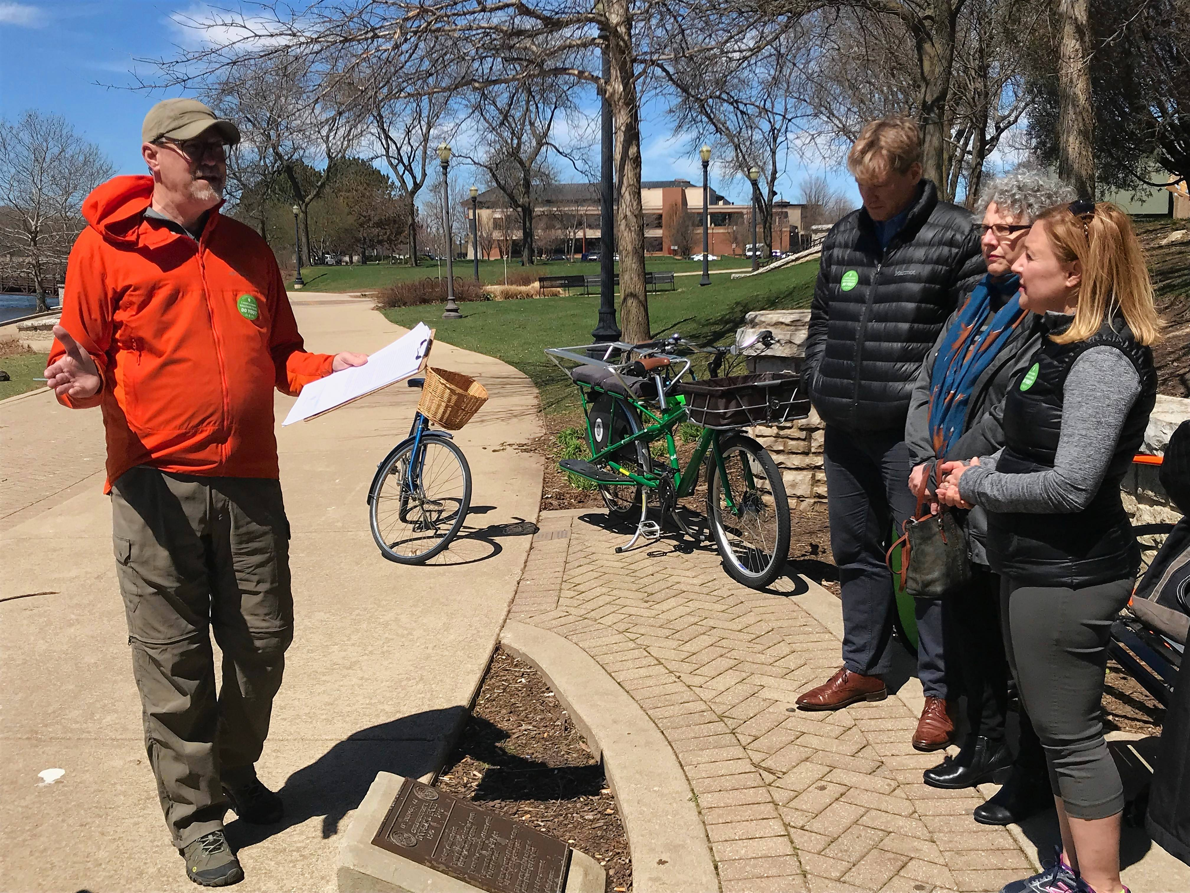 Tom Armstrong, left, a member of the Elgin parks and recreation advisory board, talks about bike friendliness Friday afternoon at an event organized by the Active Transportation Alliance along the Fox River bike trail in Elgin. To the right are, from far right, state Rep. Anna Moeller and Elgin City Council members Carol Rauschenberger and John Steffen.