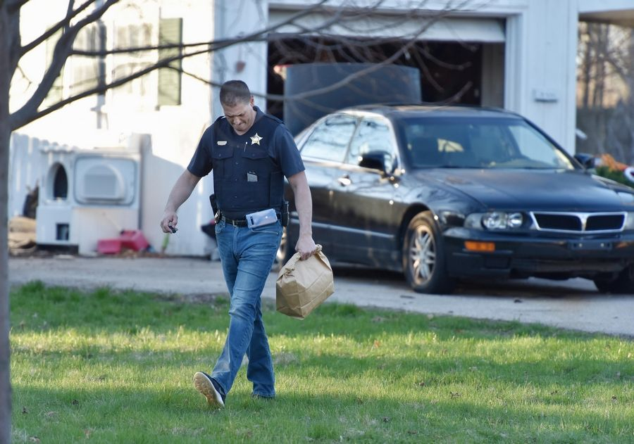 Crystal Lake police Sgt. Michael Gasparaitis carries a bag Friday from the Dole Avenue home of Andrew Freund, 5, who was last seen Wednesday night in Crystal Lake.